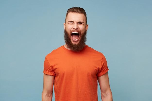 Homem grita em pé, expressão facial de raiva, isolada em azul.