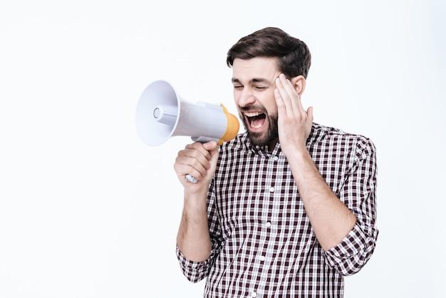 Homem grita em um megafone de dor