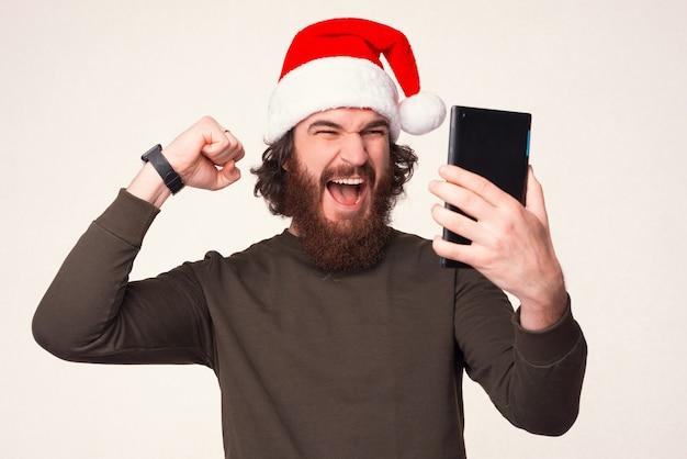 Homem gritando alegre está olhando para o tablet e fazendo o gesto vencedor.