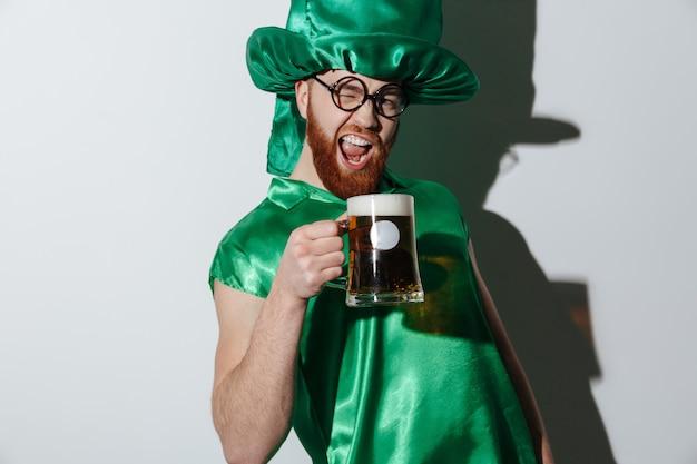Homem gritando bêbado em traje de st.patriks segurando xícara