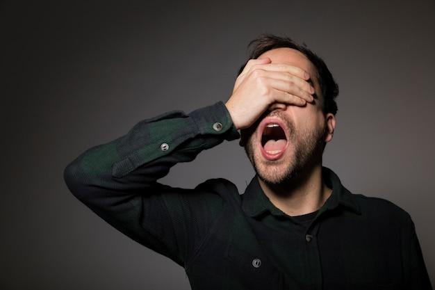 Homem gritando, cobrindo os olhos