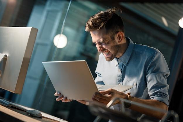 Homem gritando com laptop quebrado