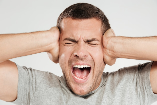 Homem gritando confuso. olhos fechados.