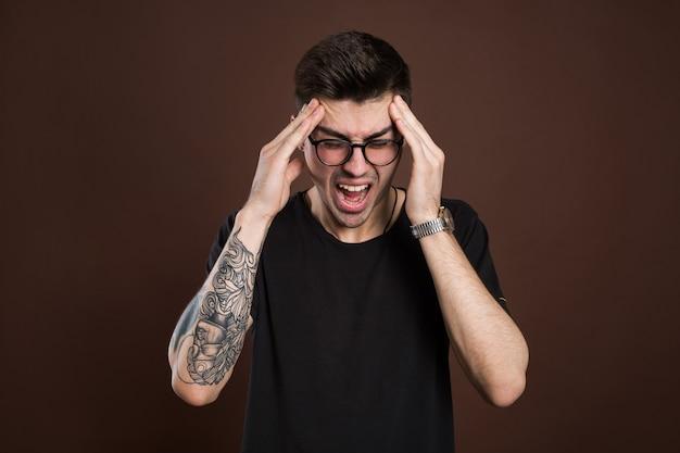 Homem gritando de boca aberta, segurando a mão na cabeça, fundo isolado, emoção de rosto