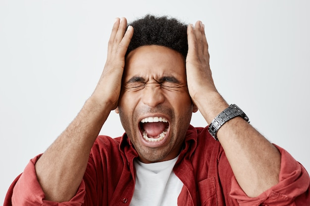 Homem gritando de enxaqueca. feche o retrato do cara infeliz de pecado preto com penteado afro em camiseta branca sob camisa casual vermelha, apertando a cabeça com as mãos da dor de cabeça.
