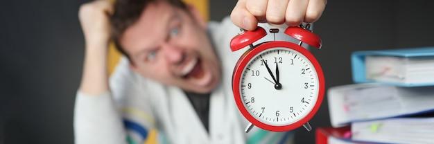 Homem gritando e segurando o despertador vermelho na mesa no escritório, close-up, reciclando o horário de trabalho