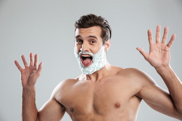 Homem gritando em pé isolado com espuma de barbear