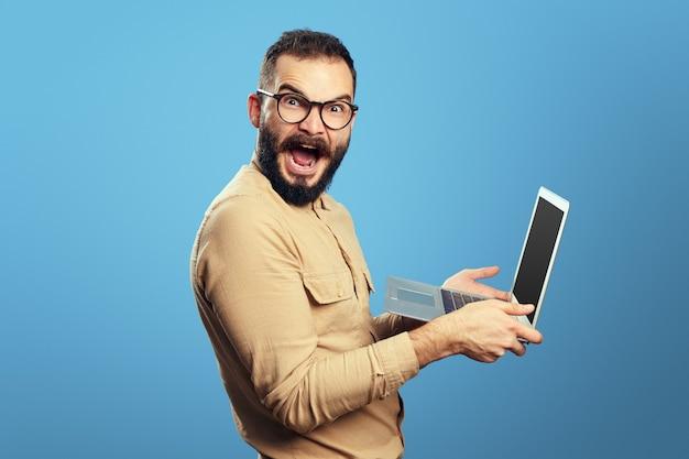 Homem gritando em triunfo segurando laptop feliz com admissão na universidade