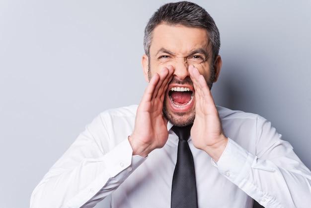 Homem gritando. homem maduro sério de camisa e gravata gritando enquanto olha para a câmera e fica de pé contra um fundo cinza