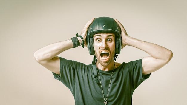 Homem gritando no capacete, segurando a cabeça