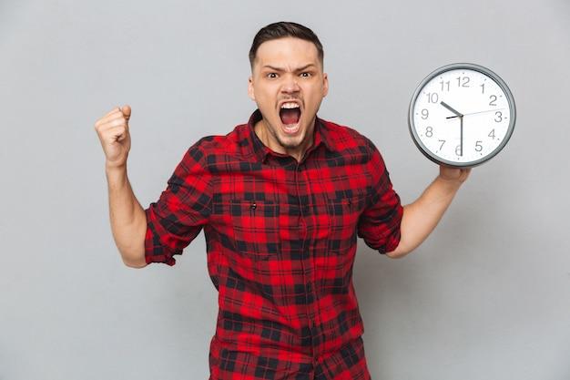 Homem gritando, segurando o relógio