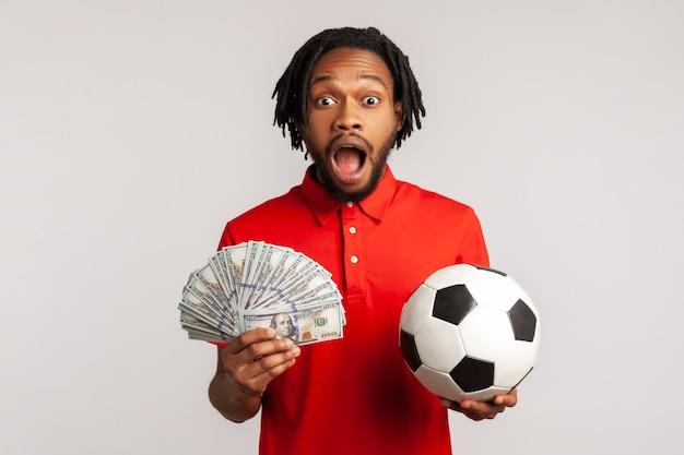 Homem gritando, segurando uma bola de futebol e notas de cem dólares, olhando a câmera, apostando e ganhando.