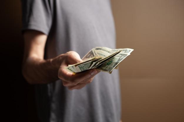 Homem guarda dinheiro e dá para outro em fundo marrom