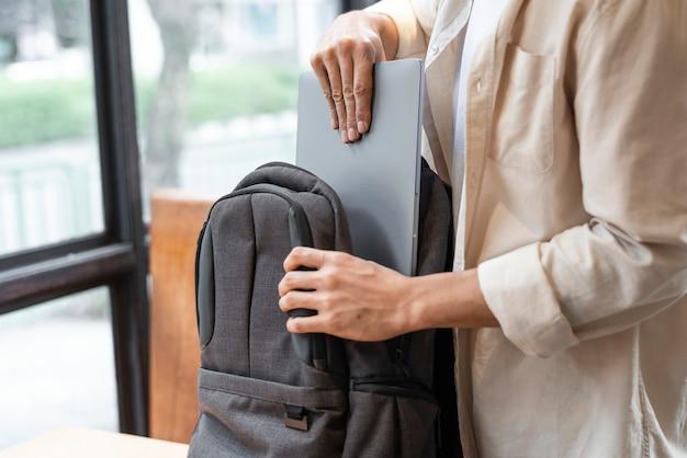 Homem guardando seu laptop em uma bolsa
