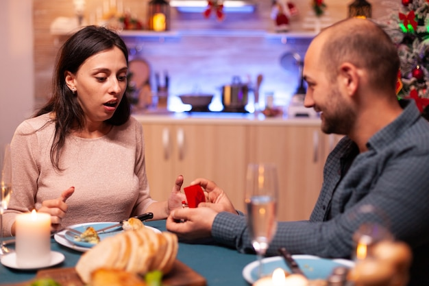 Homem haapy propondo namorada em casamento usando anel de noivado caro de diamante de luxo