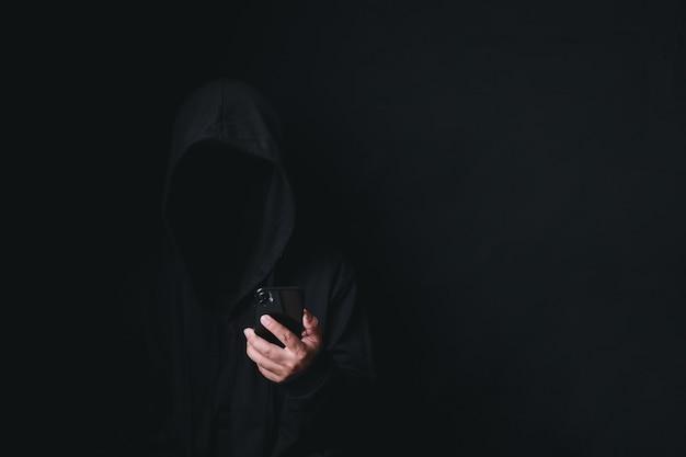 Homem hacker anônimo perigoso usando smartphone para usar encapuzado