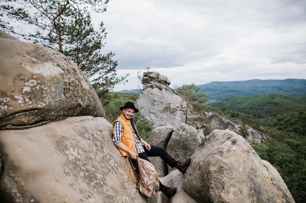 Homem hippie com chapéu e mochila nas montanhas