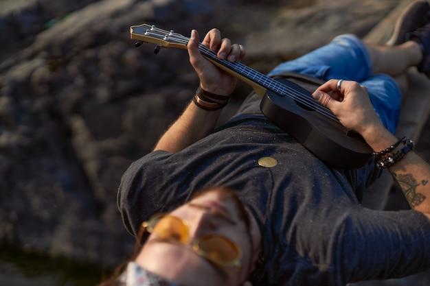 Homem hippie interessante tocando um ukulele preto deitado sobre uma ponte de madeira entre as rochas de alta qualidade.
