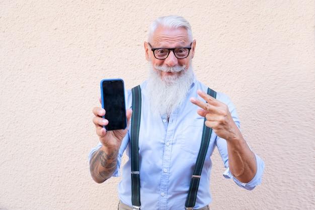 Homem hippie sênior com tatuagem se divertindo com um telefone, mostrando a felicidade, a tecnologia e o conceito de pessoas de estilo de vida idoso