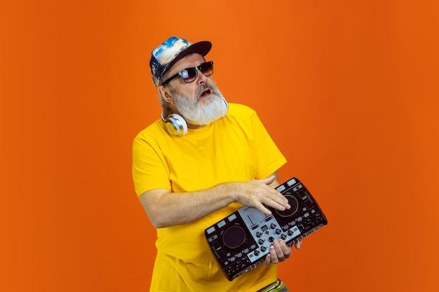 Homem hippie sênior usando dispositivos de dispositivos em fundo laranja