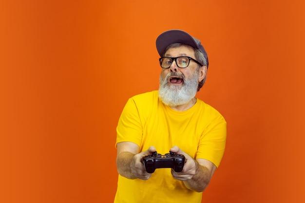 Homem hippie sênior usando dispositivos, gadgets em laranja