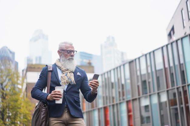 Homem hippie sênior usando telefone celular e bebendo café na cidade