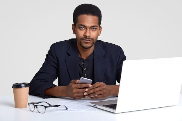 Homem hipster com pele escura, usa terno elegante, senta-se no local de trabalho, usa tecnologias modernas, mantém telefone inteligente, recebe notificação, bebe café de copo descartável, isolado no branco