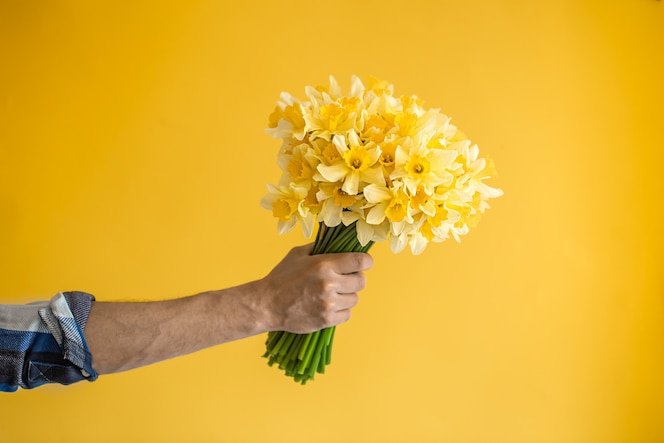 Homem hipster em uma parede amarela em uma camisa e um buquê de flores.