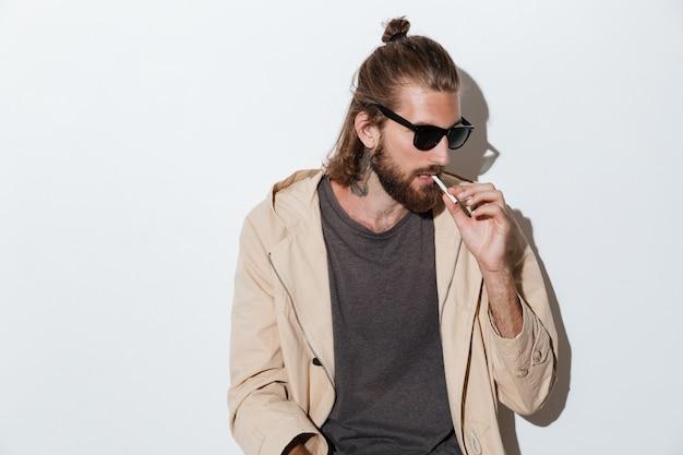 Homem hipster olhando de lado isolado sobre a parede