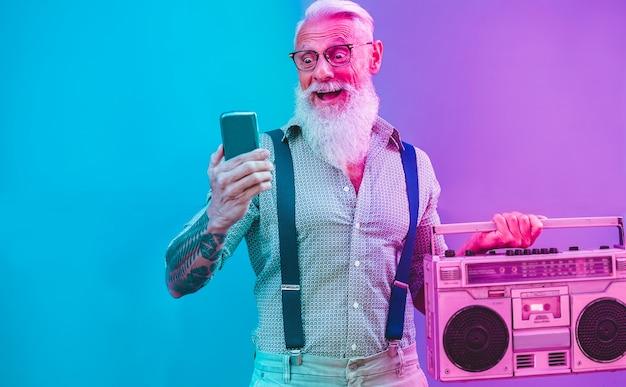 Homem hipster sênior, usando o aplicativo de smartphone para criar lista de reprodução - cara de tatuagem na moda se divertindo com a tecnologia do telefone móvel - tecnologia e conceito de estilo de vida alegre e idoso - filtro roxo e azul radial