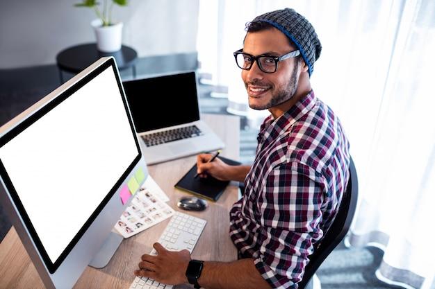 Homem hipster sorridente posando enquanto está sentado na mesa do computador