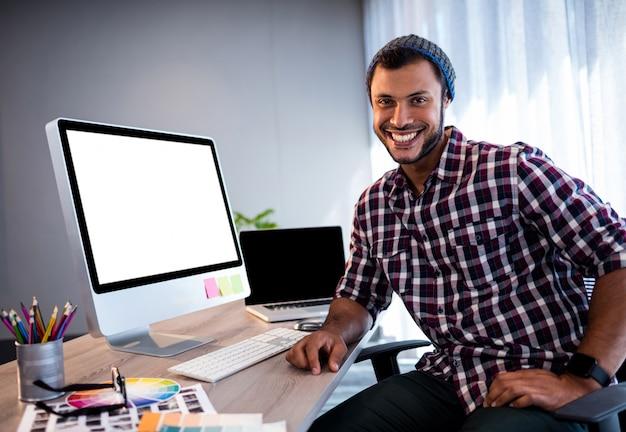 Homem hipster sorridente posando na mesa do computador no estúdio