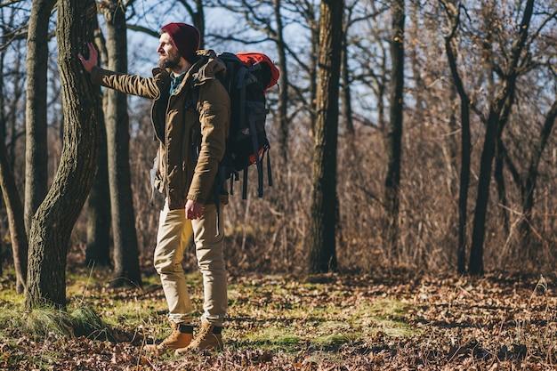 Homem hipster viajando com uma mochila na floresta de outono vestindo uma jaqueta quente, chapéu, turista ativo, explorando a natureza na estação fria