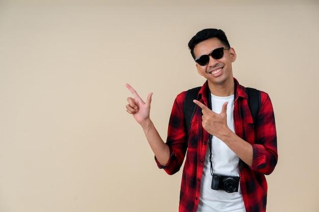 Homem hipster viajante sorrindo e apontando sobre fundo de cor creme