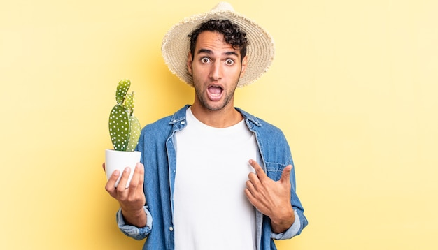 Homem hispânico bonito chocado e surpreso com a boca bem aberta, apontando para o autoprocurador e o conceito de cacto