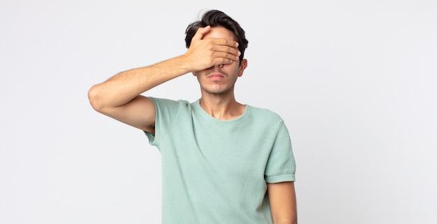 Homem hispânico bonito cobrindo os olhos com uma das mãos, sentindo-se assustado ou ansioso, imaginando ou esperando cegamente por uma surpresa