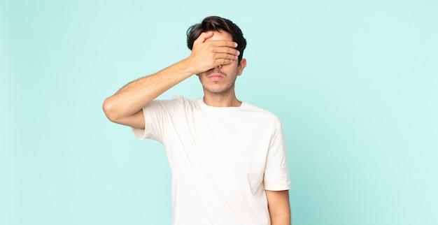 Homem hispânico bonito cobrindo os olhos com uma mão, sentindo-se assustado ou ansioso, imaginando ou esperando cegamente por uma surpresa