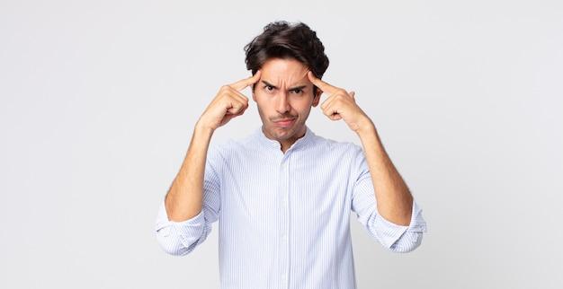 Homem hispânico bonito com um olhar sério e concentrado, fazendo um brainstorming e pensando sobre um problema desafiador