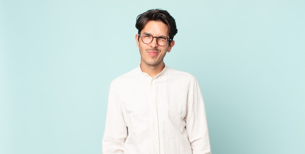 Homem hispânico bonito com uma aparência feliz e amigável, sorrindo e piscando os olhos para você com uma atitude positiva