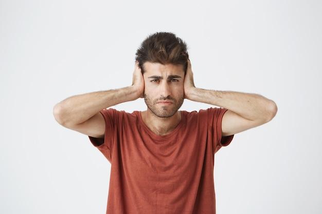 Homem hispânico bonito frustrado em camiseta vermelha, conectando os ouvidos com as mãos, sendo exausto de sons altos de apartamentos vizinhos à noite.