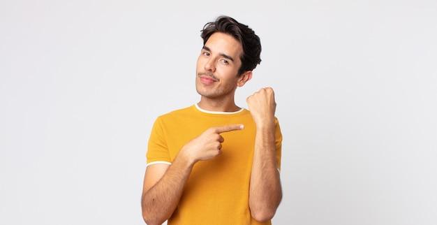Homem hispânico bonito, impaciente e zangado, apontando para o relógio, pedindo pontualidade, quer ser pontual