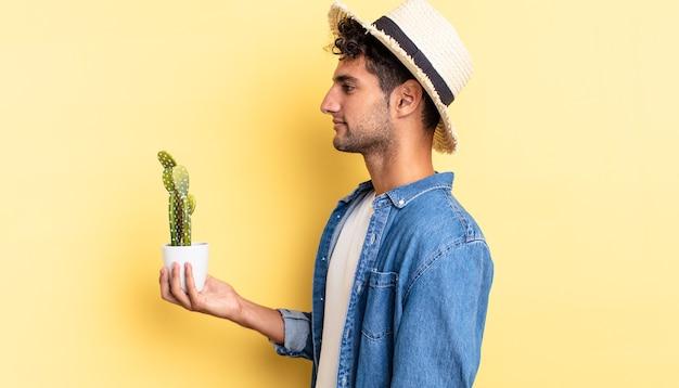 Homem hispânico bonito na vista de perfil, pensando, imaginando ou sonhando acordado com o conceito de agricultor e cacto