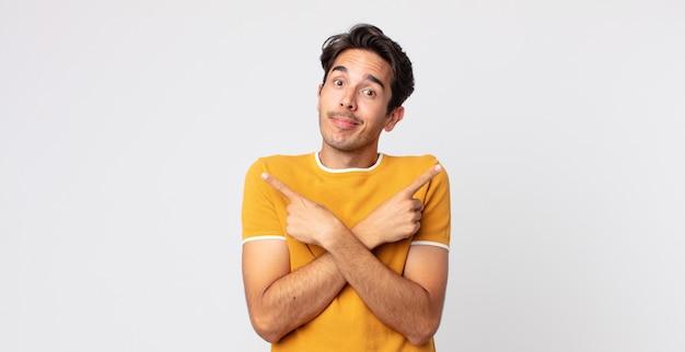 Homem hispânico bonito parecendo perplexo e confuso, inseguro e apontando em direções opostas com dúvidas