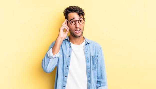 Homem hispânico bonito parecendo surpreso ao perceber um novo pensamento, ideia ou conceito