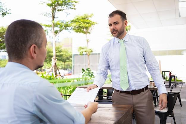 Homem hispânico bonito sério, trazendo papéis para gerente