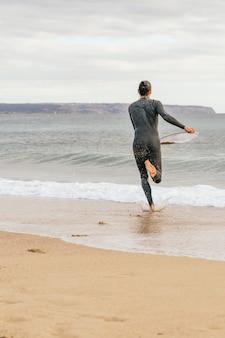 Homem hispânico caucasiano correndo pela praia para pegar uma onda com um skimboard nas mãos