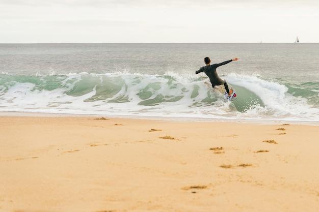 Homem hispânico caucasiano surfando em um skimboard ao pôr do sol na praia