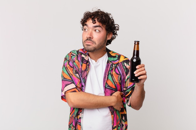 Homem hispânico com cerveja encolhendo os ombros, sentindo-se confuso e incerto, duvidando com os braços cruzados e olhar perplexo