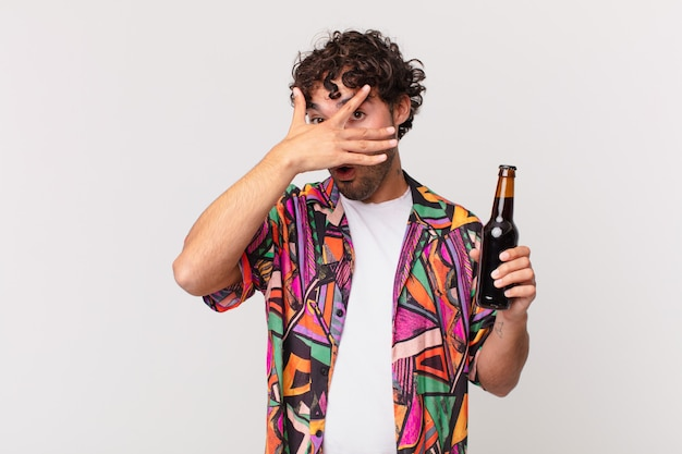 Homem hispânico com cerveja parecendo chocado, assustado ou apavorado, cobrindo o rosto com a mão e espiando por entre os dedos