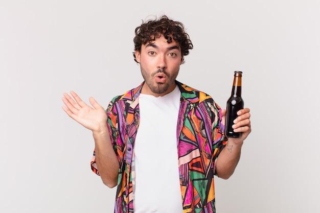 Homem hispânico com cerveja parecendo surpreso e chocado, com o queixo caído segurando um objeto com a mão aberta na lateral